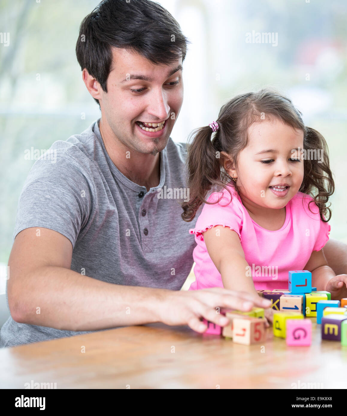 Happy father and daughter playing with building blocks at table in house - Stock Image