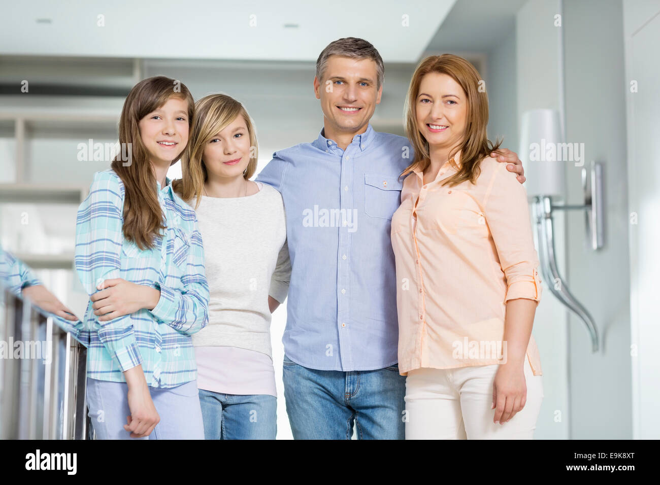 Portrait of happy parents with daughters standing together at home - Stock Image