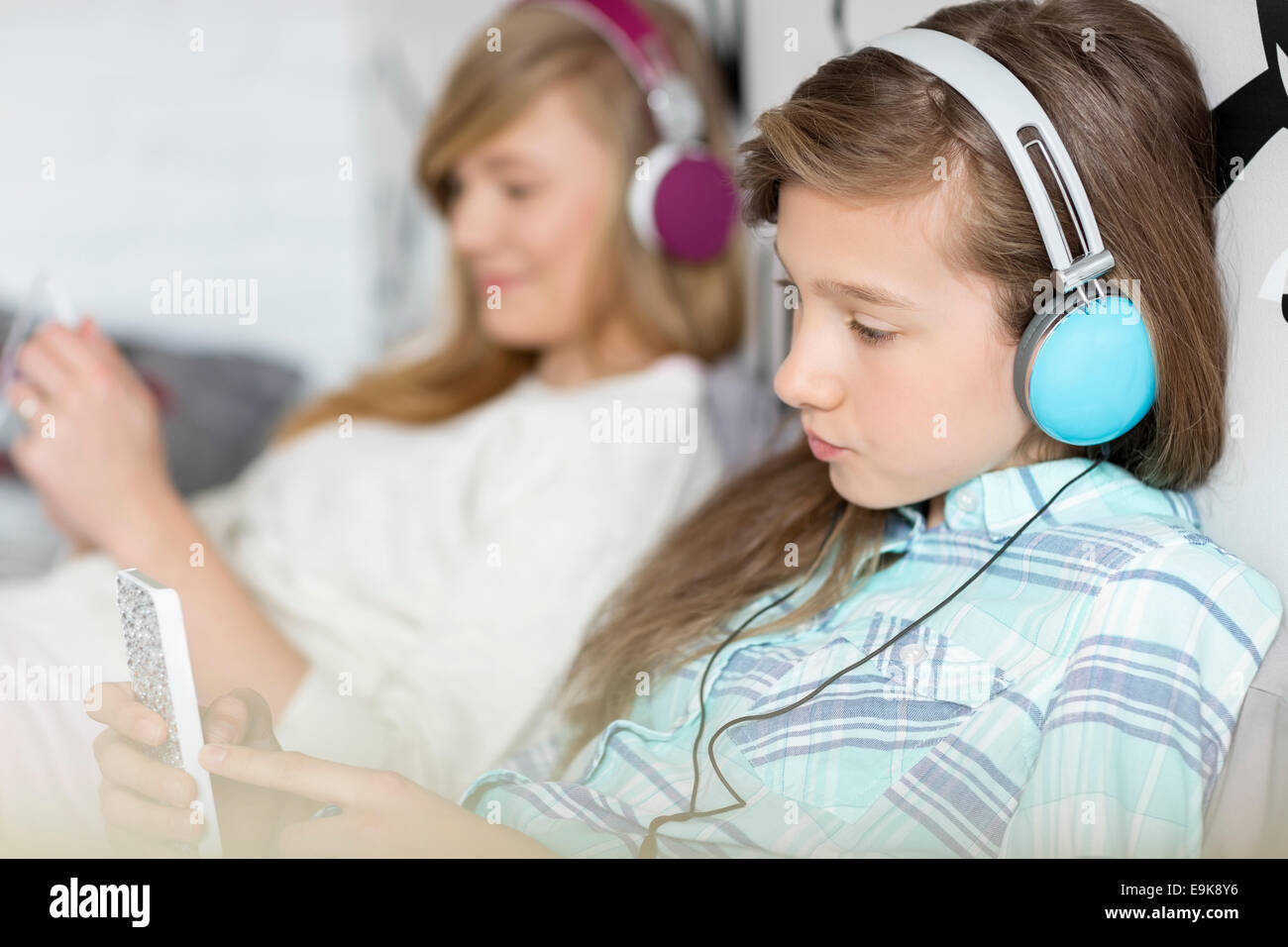 Sisters listening music through headphones at home - Stock Image