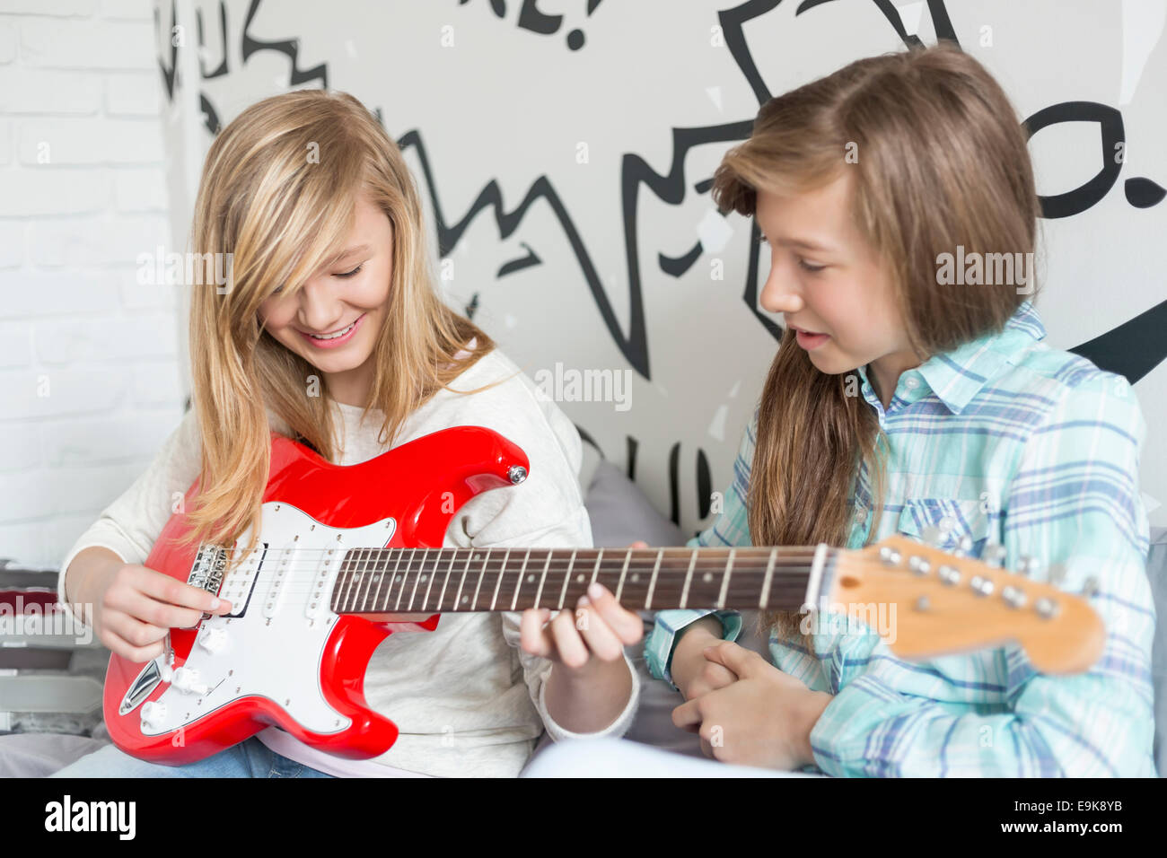 Girl listening to sister playing electric guitar at home - Stock Image