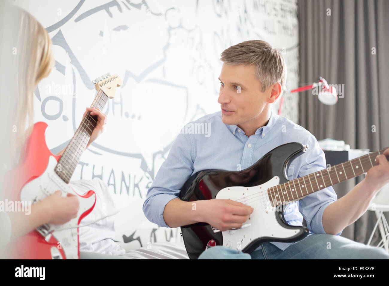 Father and daughter playing electric guitars at home - Stock Image