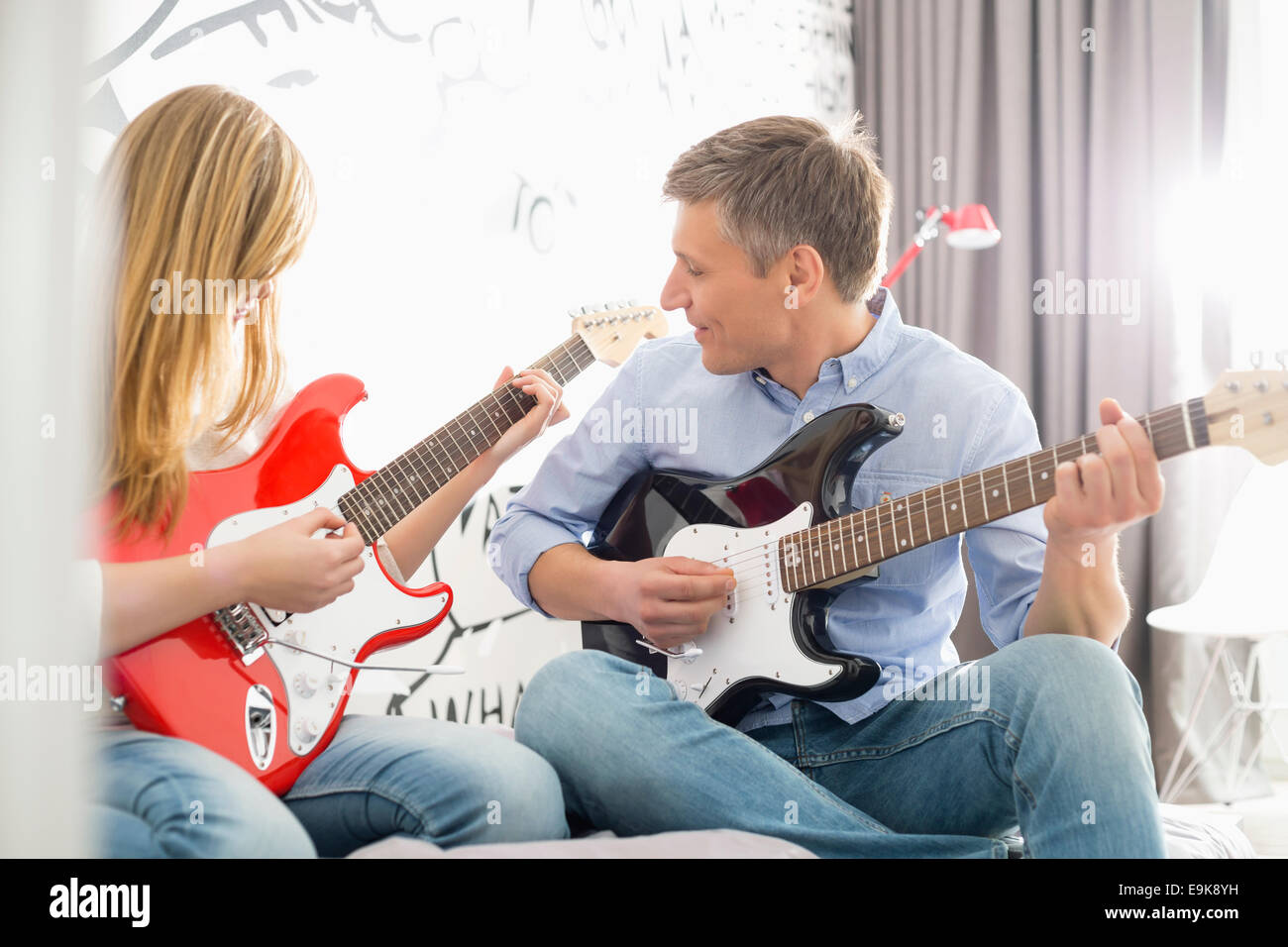 Middle-aged man with daughter playing guitars at home - Stock Image