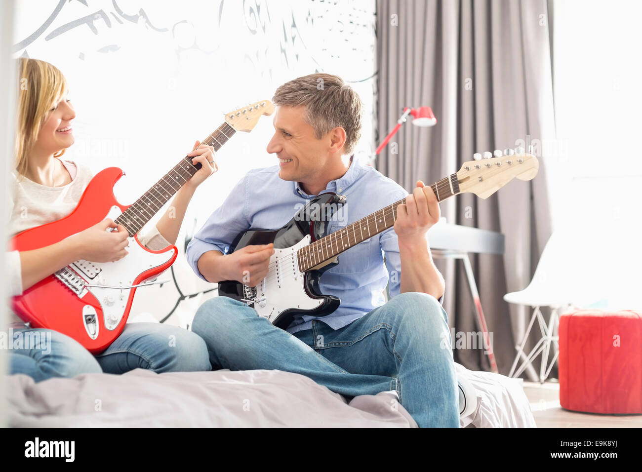 Happy father and daughter playing guitars at home - Stock Image