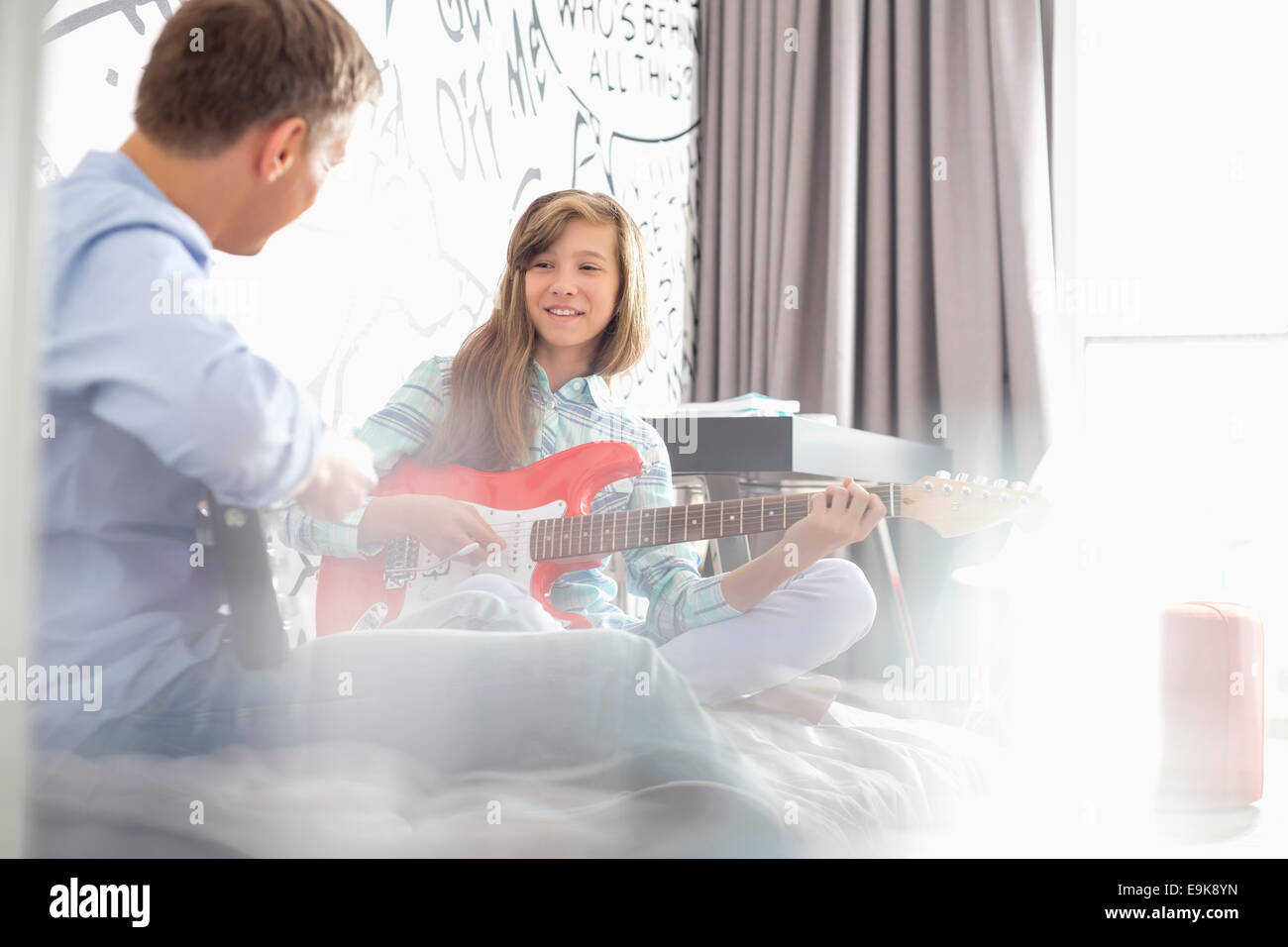 Girl with father playing electric guitars at home - Stock Image