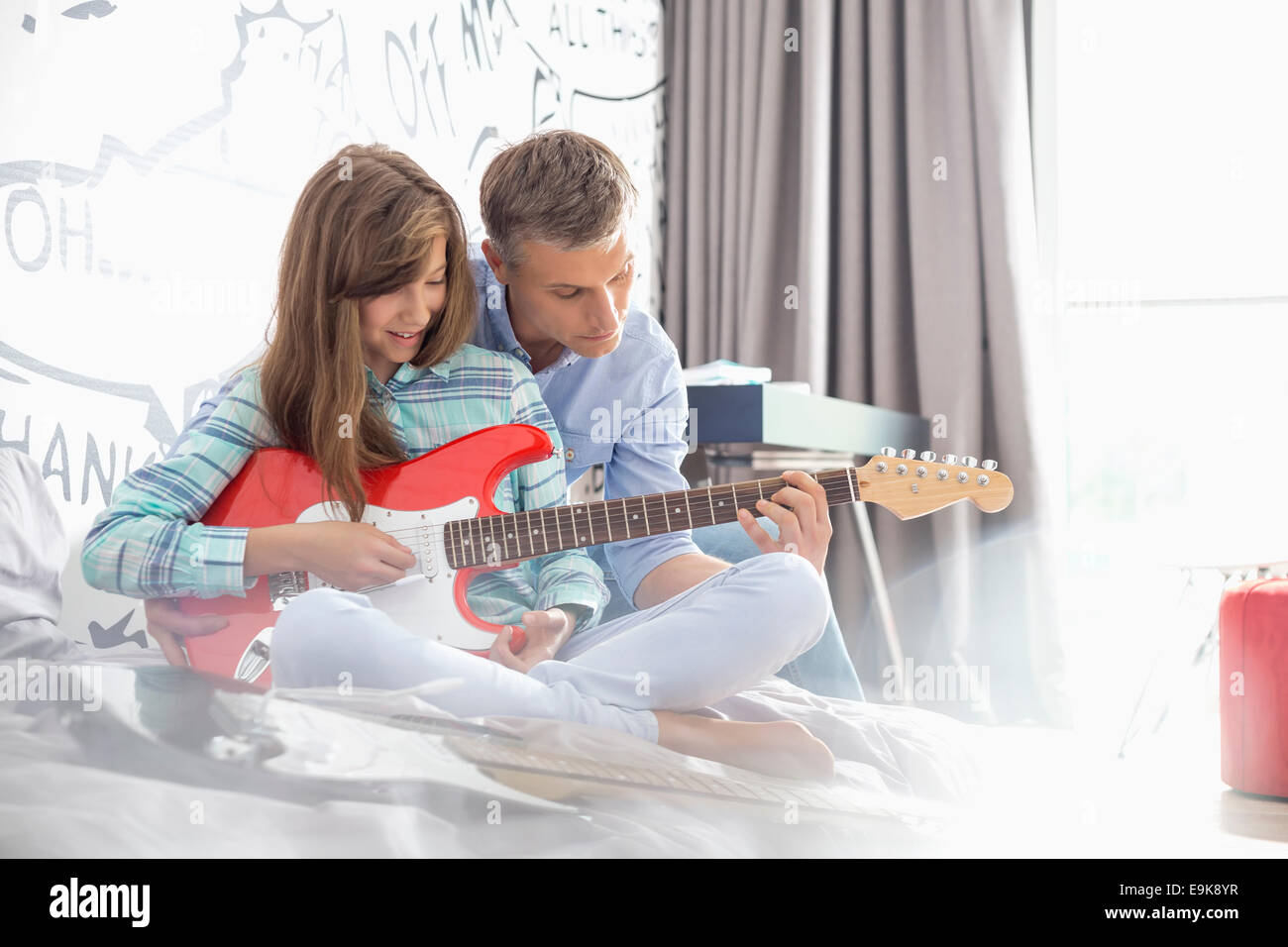 Father teaching daughter to play electric guitar at home - Stock Image