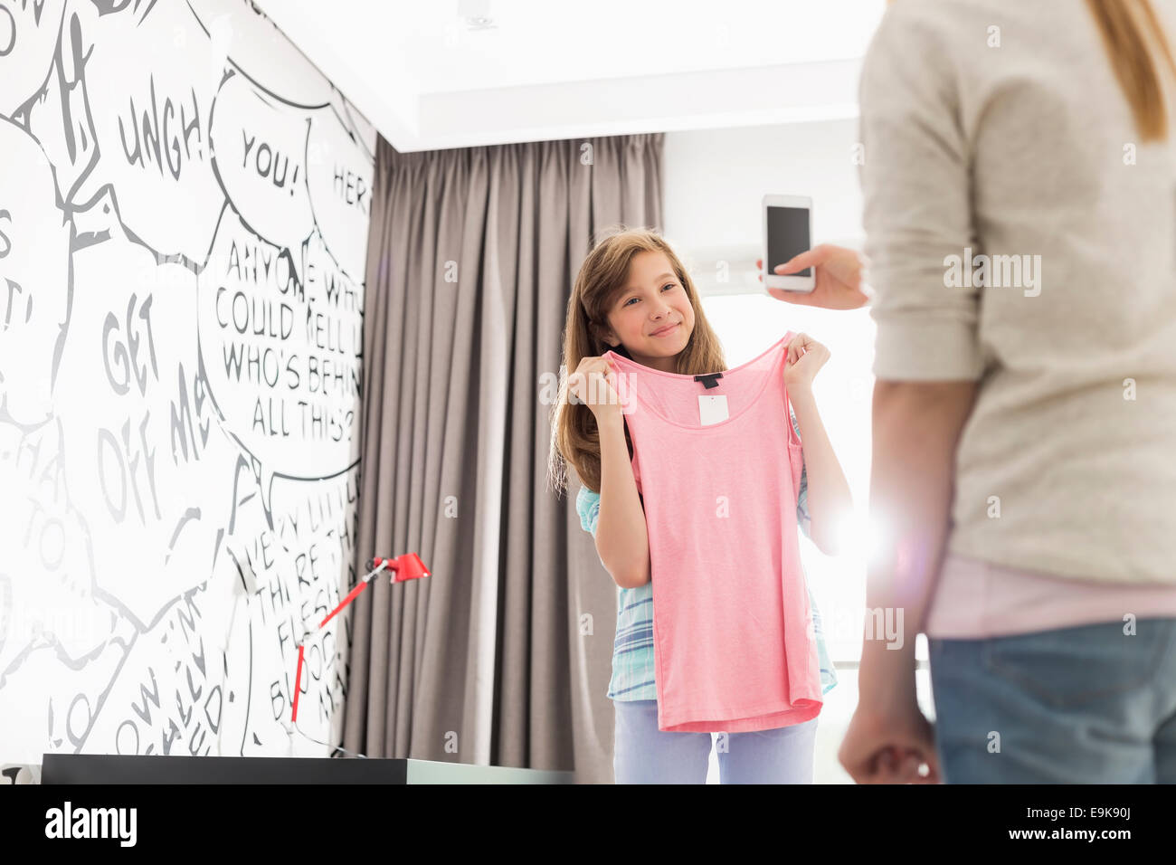 Girl trying on clothes while sister photographing her at home - Stock Image