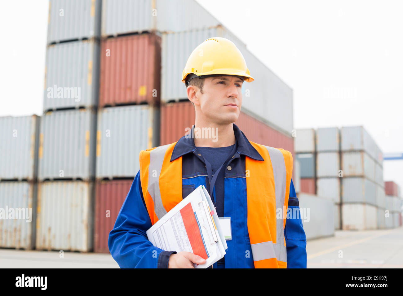 Mid adult man with clipboard in shipping yard - Stock Image