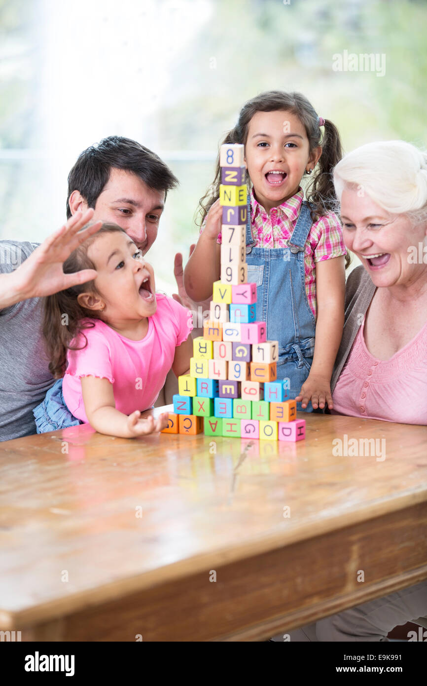 Happy multi generation family with arranged building blocks at table in house - Stock Image