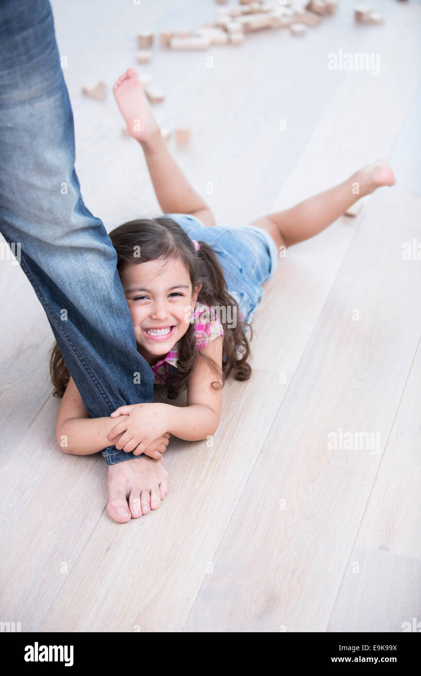 Portrait of happy girl being dragged by father on hardwood floor - Stock Image