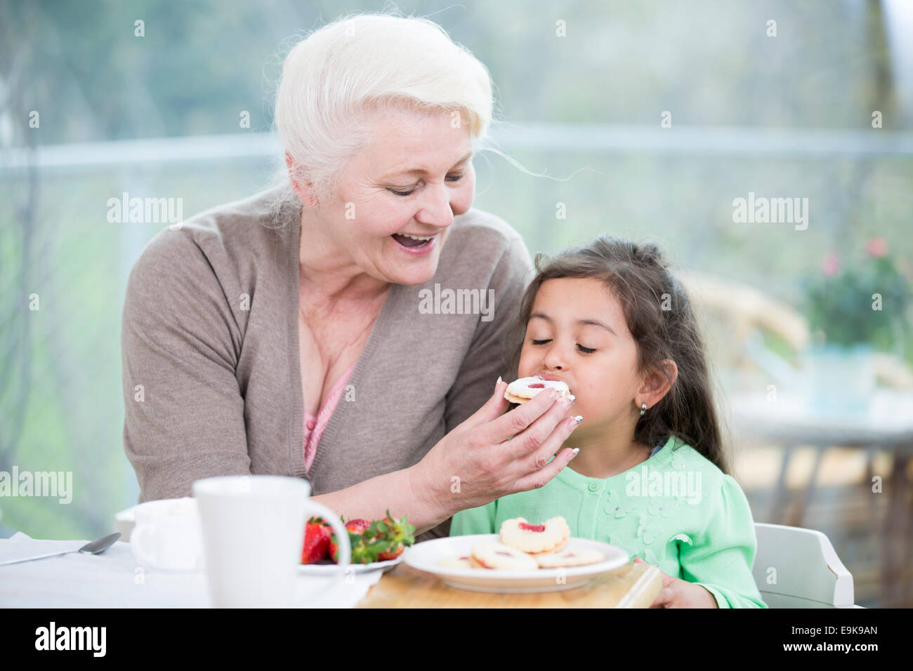 Happy senior woman feeding cookie to granddaughter at home - Stock Image