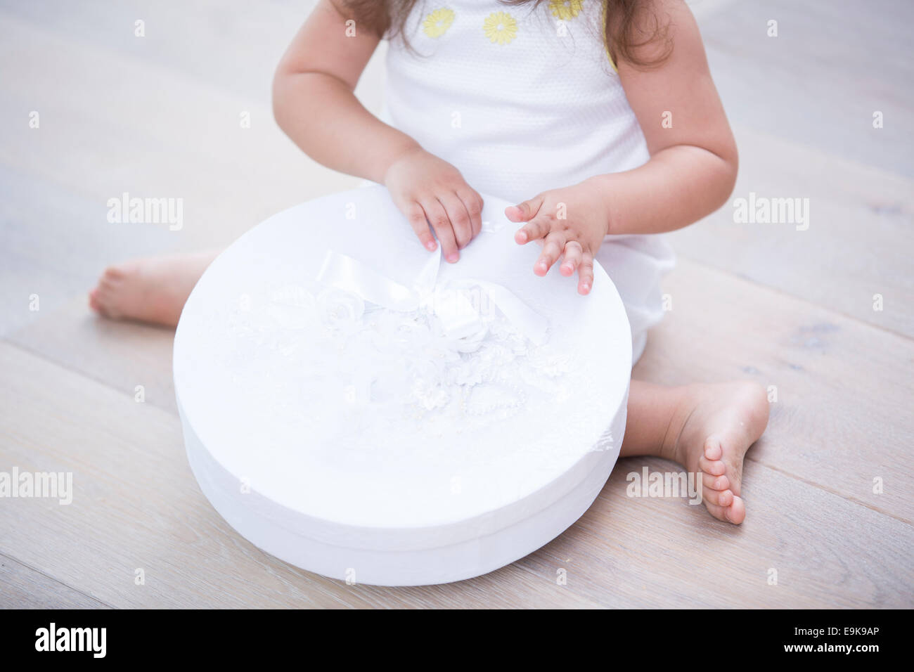 Low section of little girl opening gift box on floor at home - Stock Image