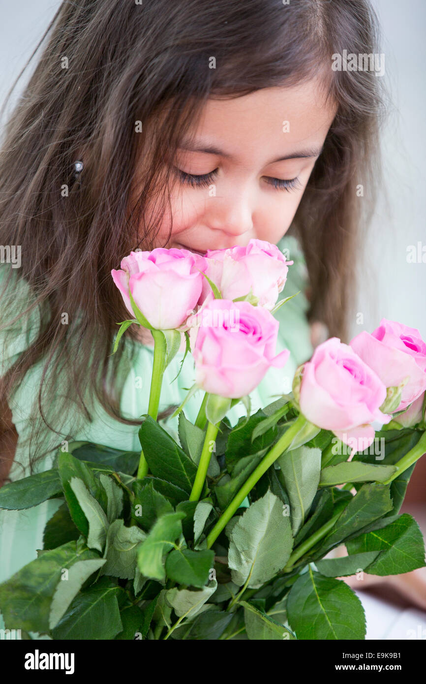 Cute girl smelling roses at home - Stock Image
