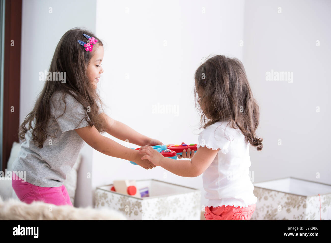 Side view of sisters fighting for toy guitar at home - Stock Image