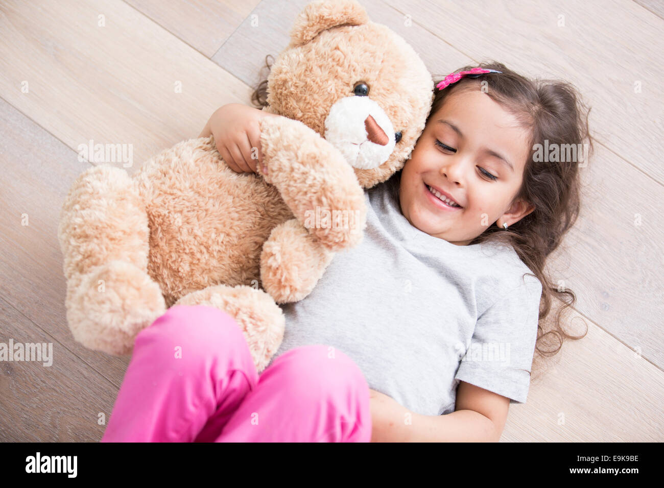 Girl with teddy bear lying on wooden floor at home - Stock Image
