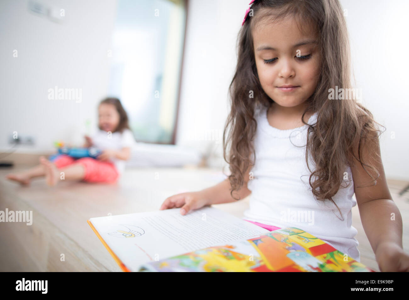 Cute girl reading book with sister in background at home - Stock Image
