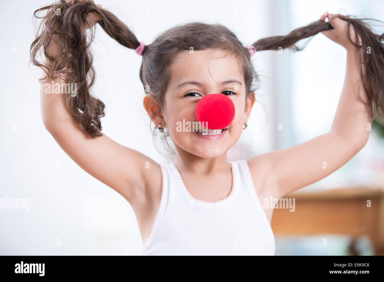 Portrait of playful little girl wearing clown nose holding pigtails at home - Stock Image