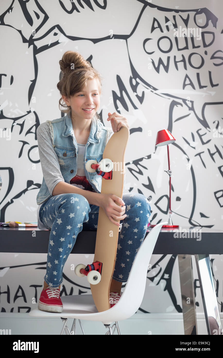 Full-length of girl with skateboard sitting on study table at home - Stock Image