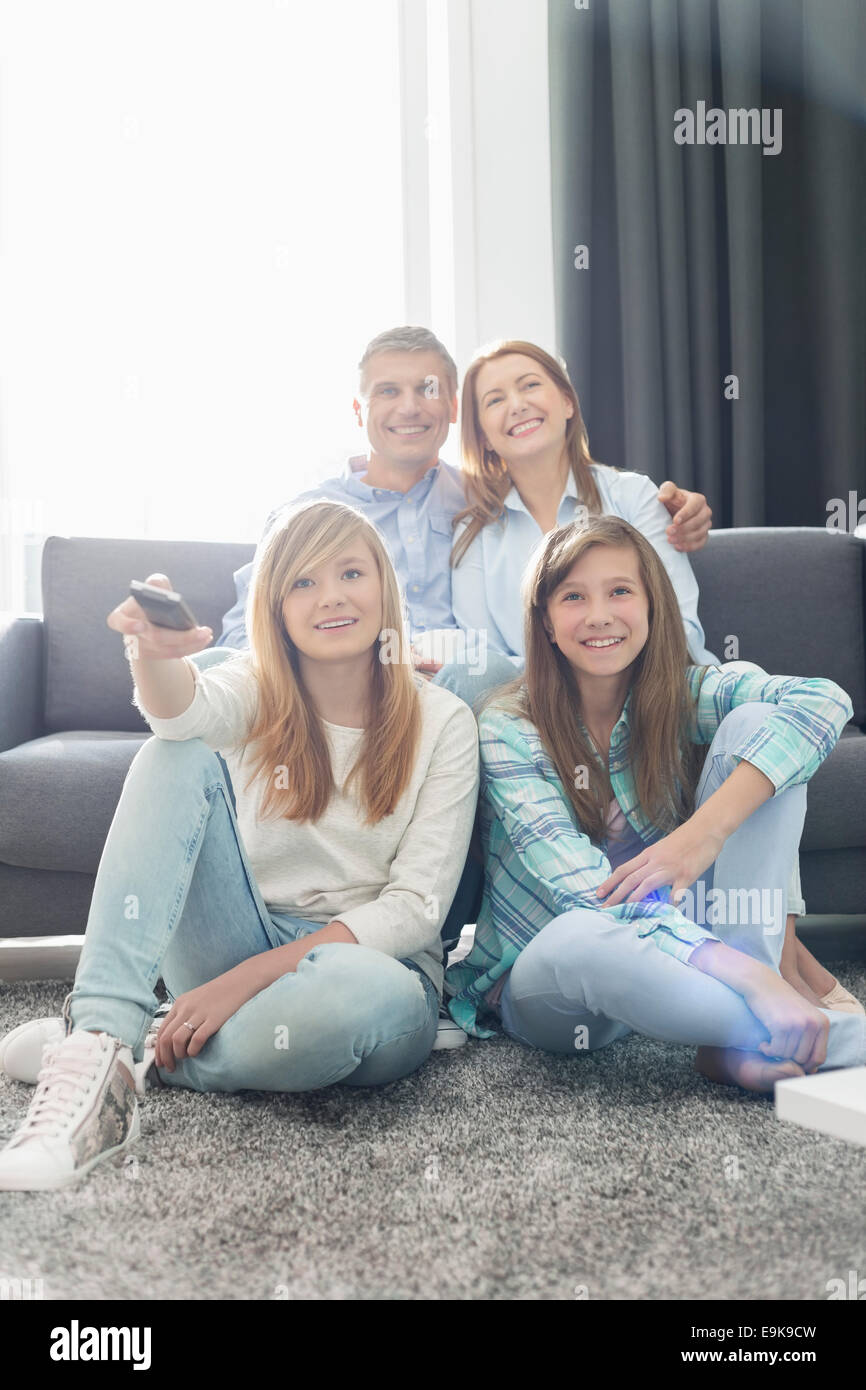 Happy family of four watching TV together at home Stock Photo