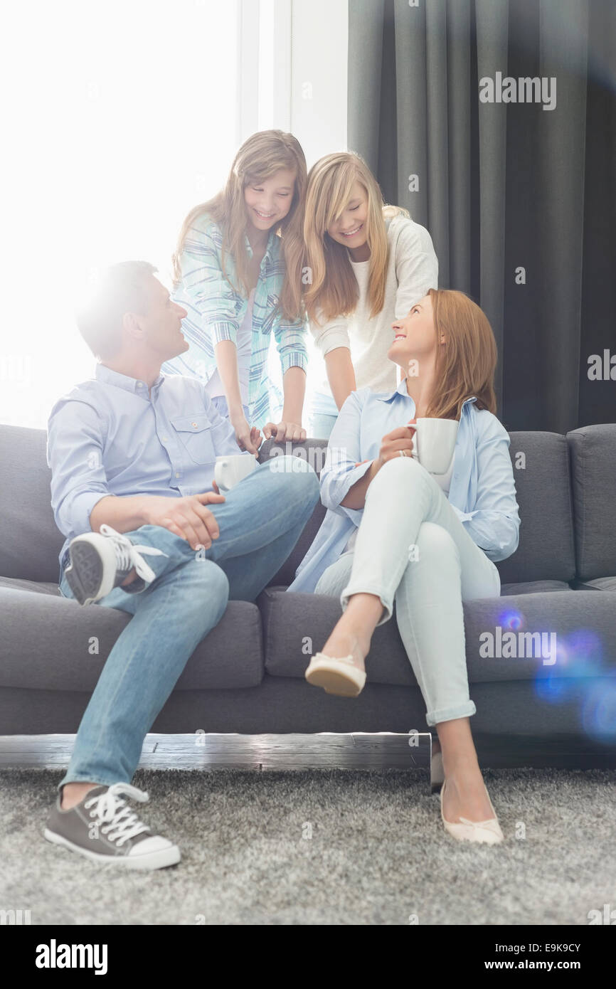 Happy parents with daughters spending quality time in living room - Stock Image