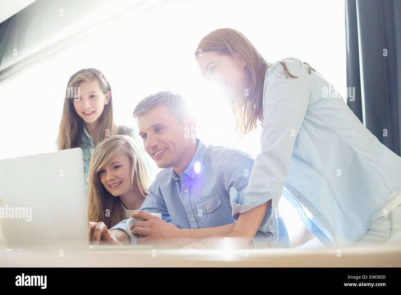 Happy parents with daughters using laptop at home - Stock Image