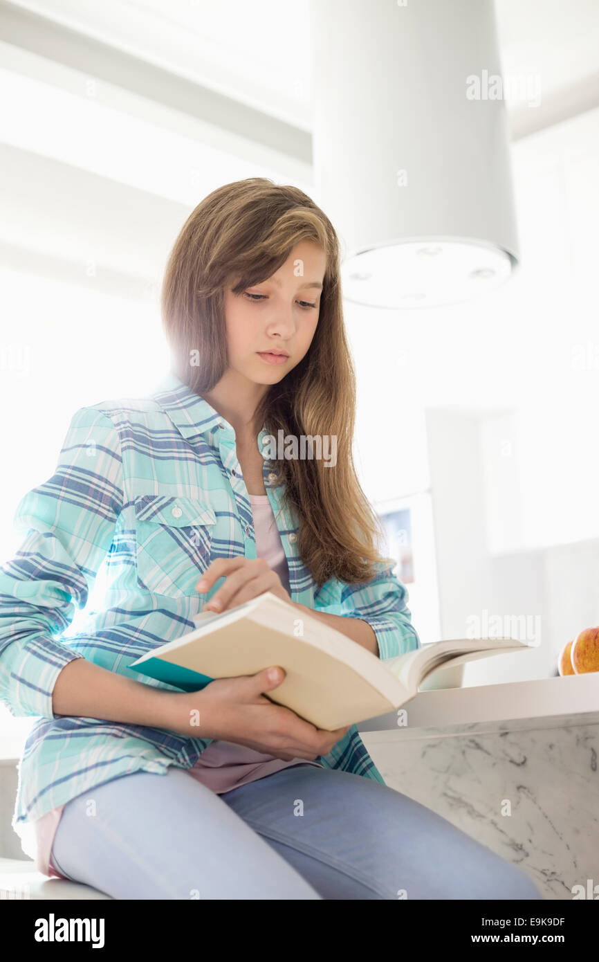 Girl reading book at home - Stock Image