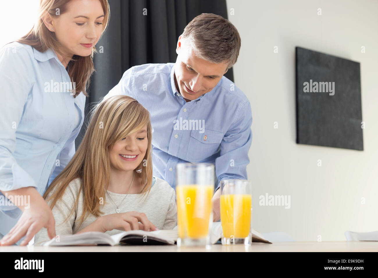 Happy parents assisting daughter in homework at home - Stock Image