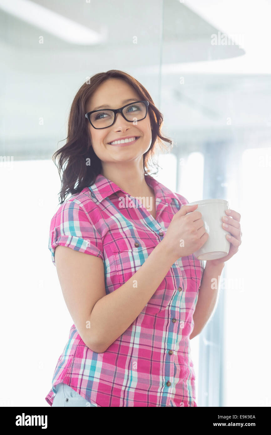 Happy businesswoman looking away while holding coffee mug in creative office - Stock Image
