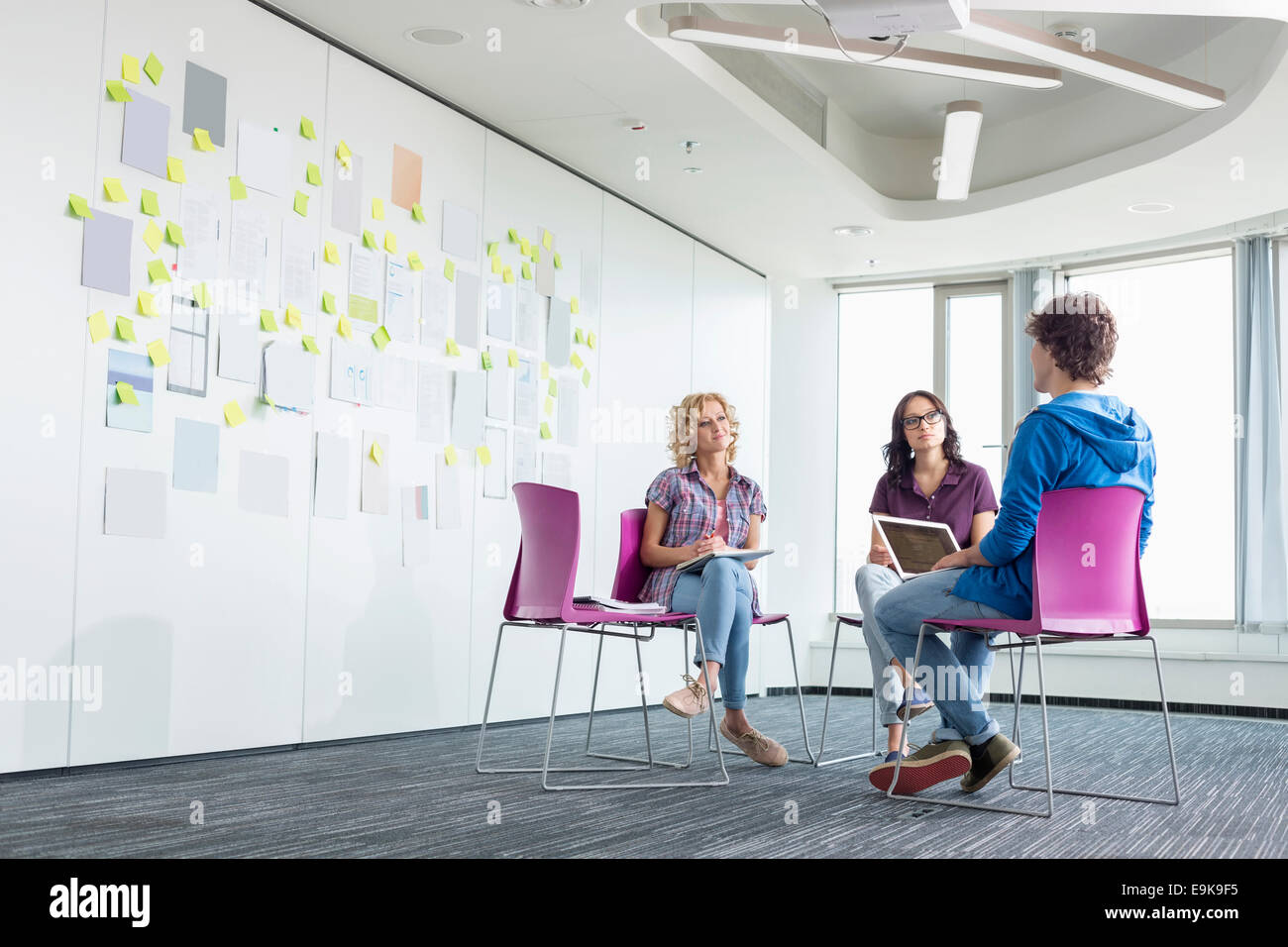 Businesspeople discussing in creative office space - Stock Image