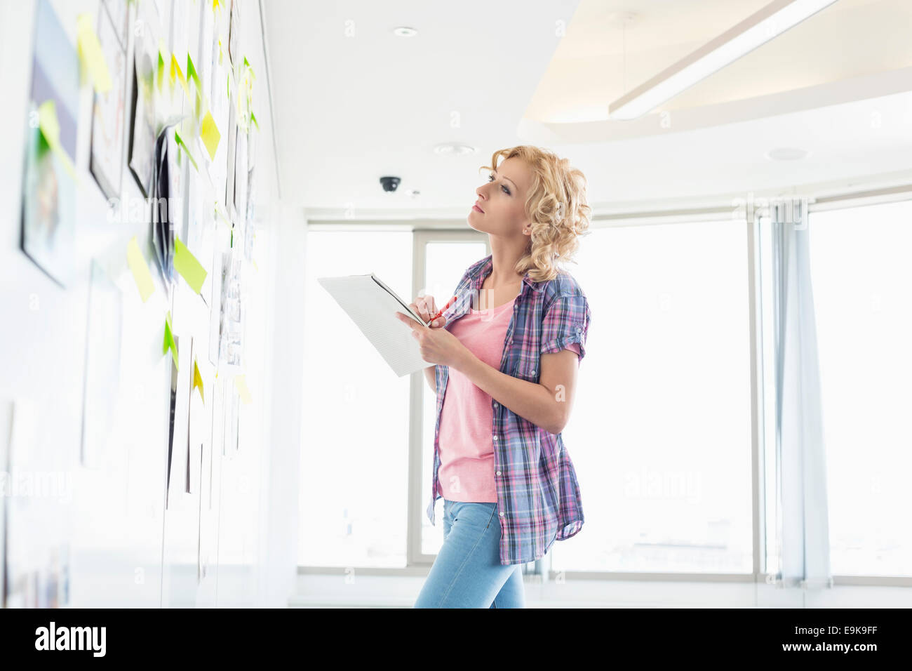 Creative businesswoman looking at papers stuck on wall while writing notes in office - Stock Image