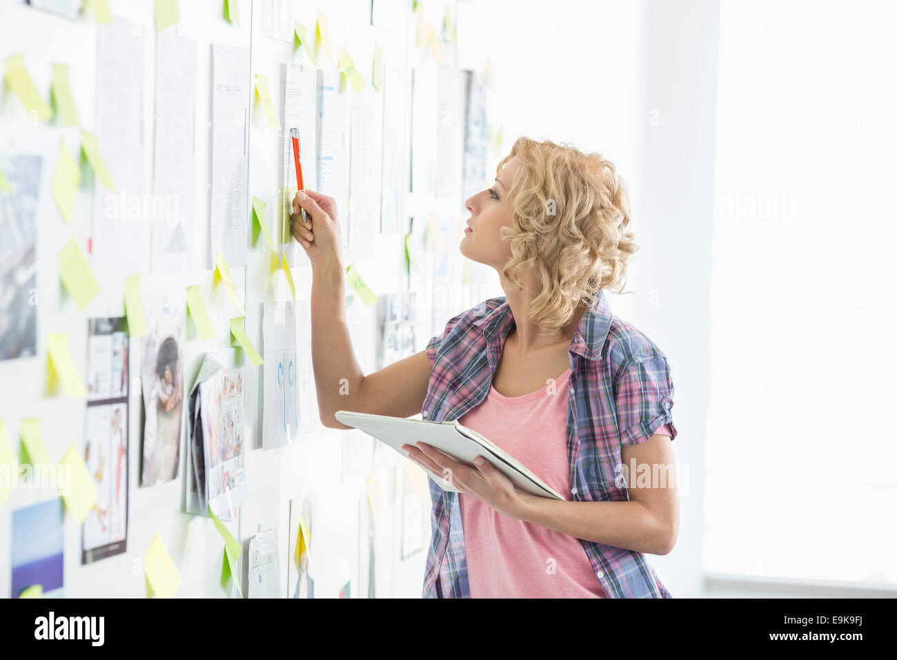 Creative businesswoman analyzing papers stuck on wall in office - Stock Image