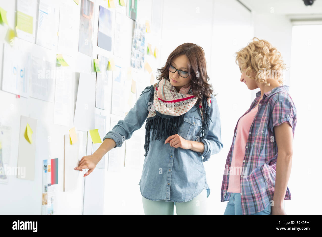 Businesswomen discussing over papers stuck on wall in creative office - Stock Image
