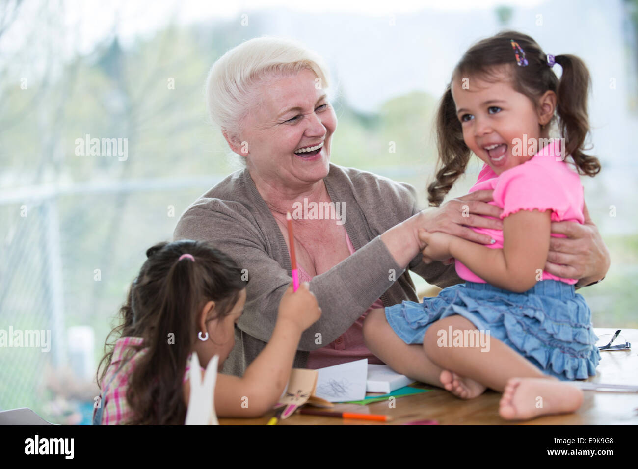 Happy senior woman having quality time with granddaughters at home - Stock Image