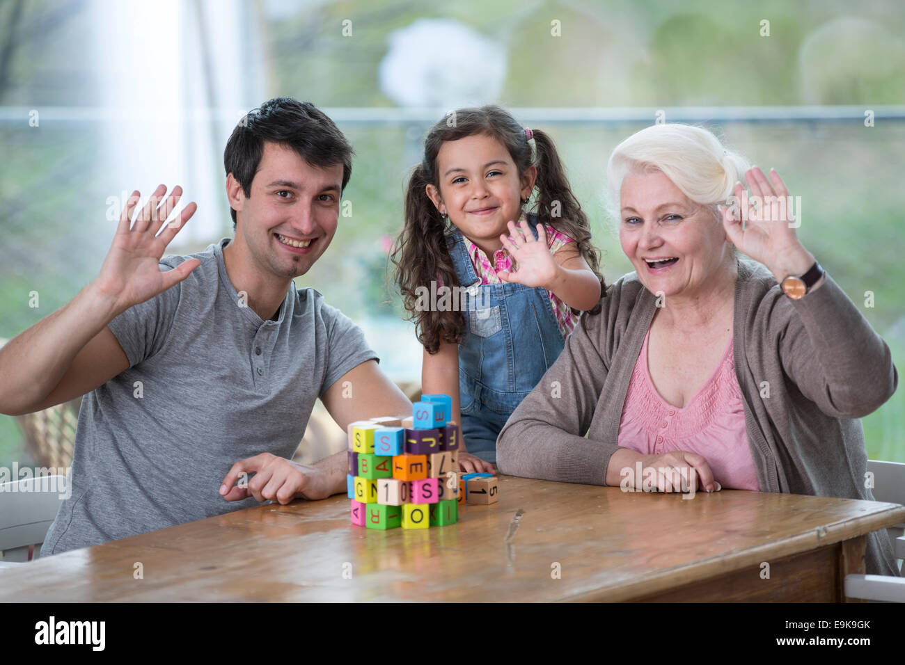 Portrait of senior woman with son and granddaughter waving hands at table - Stock Image