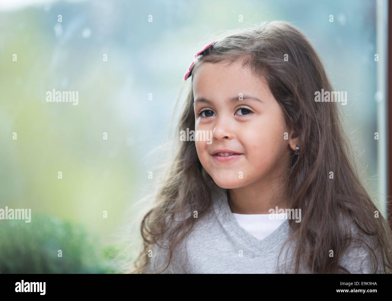 Portrait of cute little girl against glass window at home - Stock Image