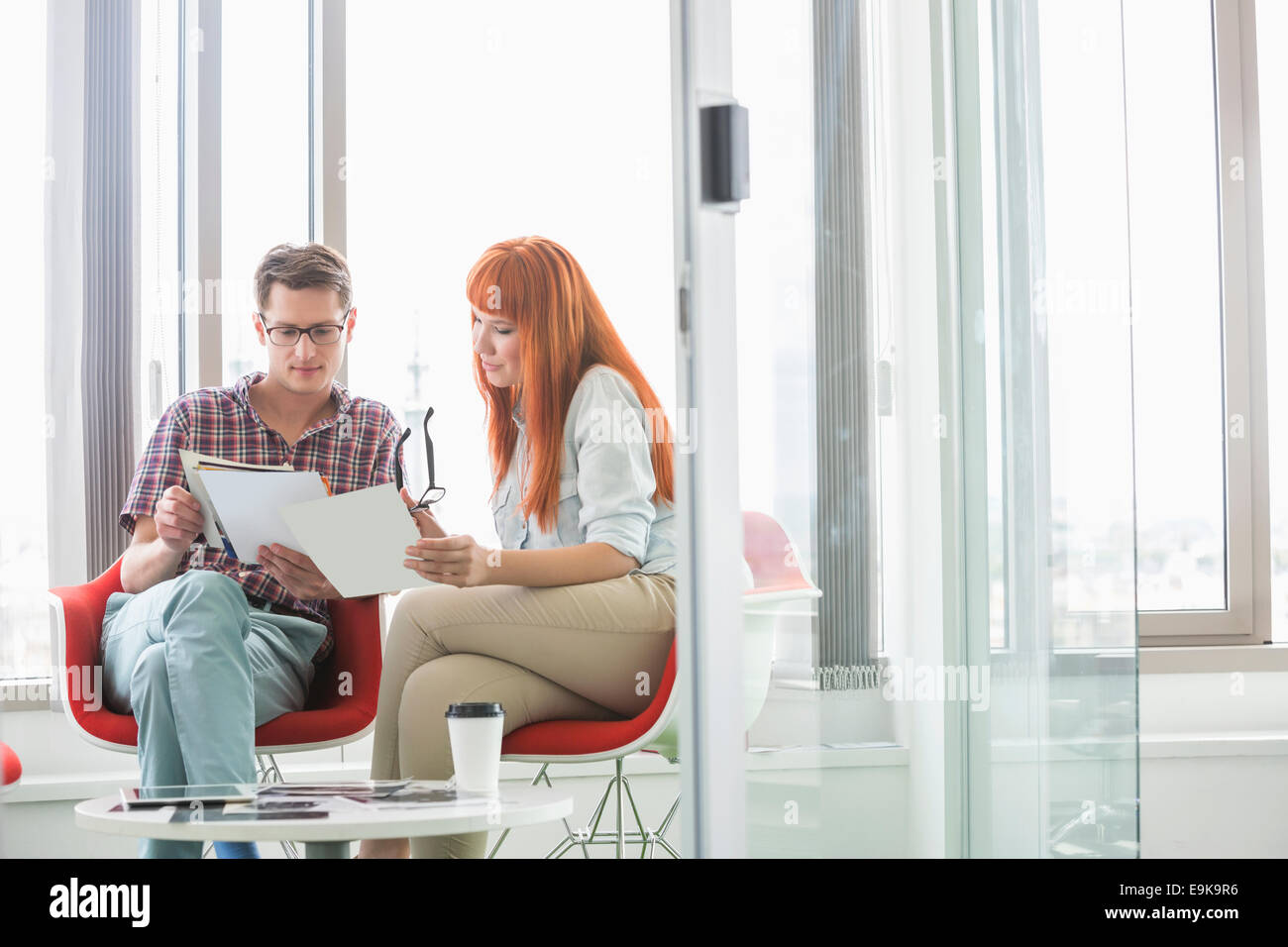 Business colleagues analyzing documents in creative office - Stock Image