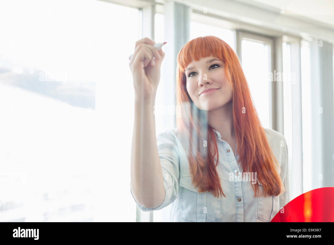 Creative businesswoman writing on glass wall in office - Stock Image
