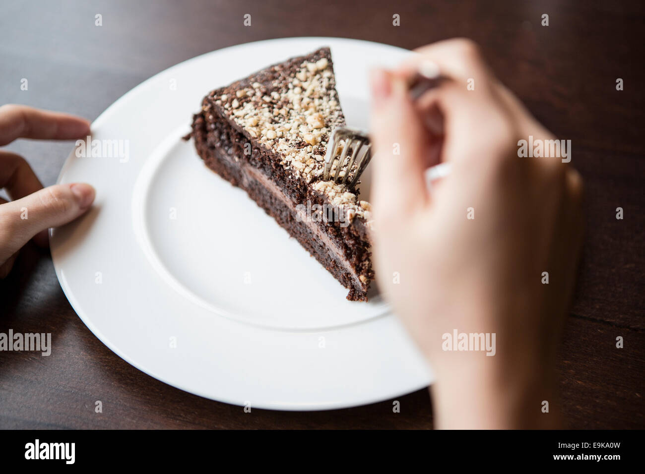 Close-up of woman's hand holding fork to chocolate pastry Stock Photo
