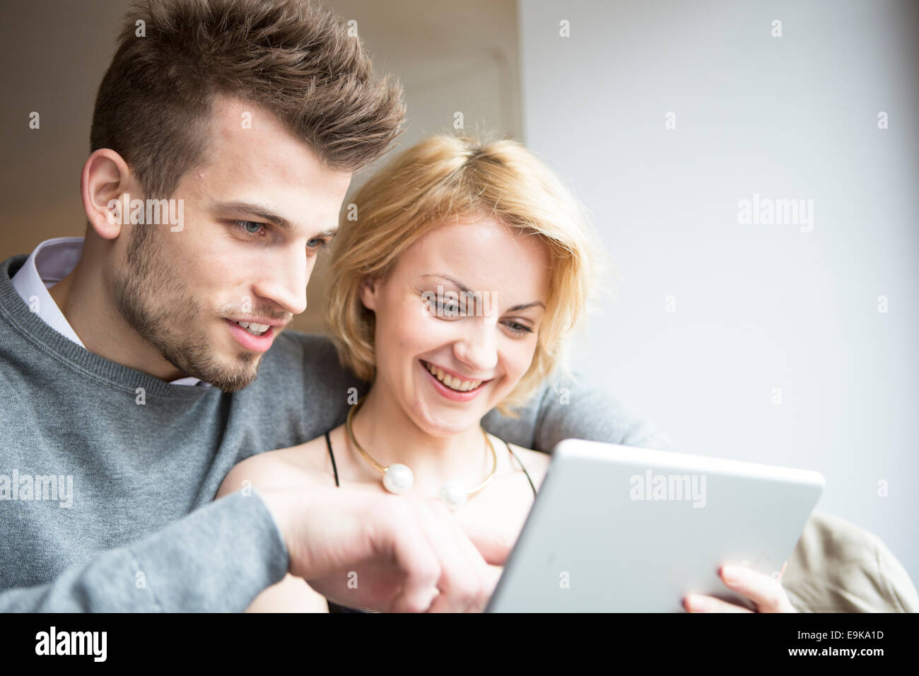 Happy young couple using digital tablet in cafe Stock Photo