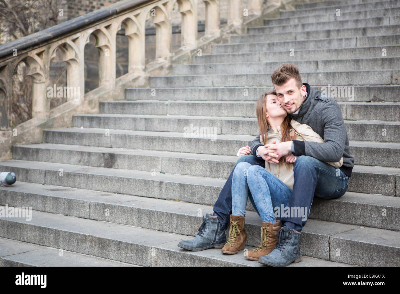 Full length of loving woman kissing man while sitting on steps outdoors - Stock Image