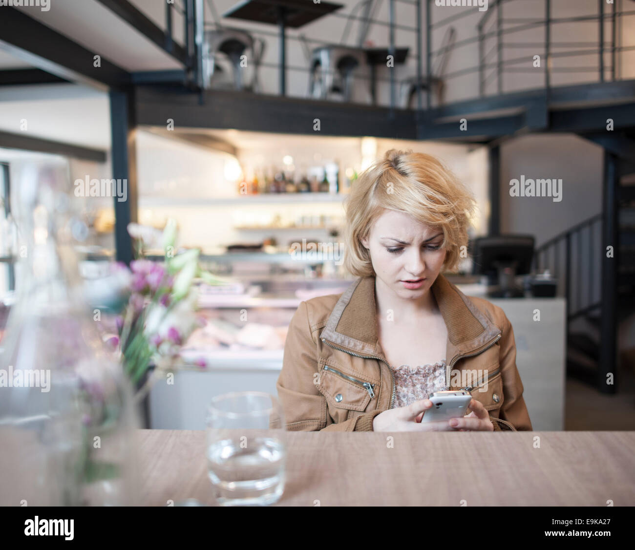 Worried young woman reading text message on cell phone in cafe - Stock Image