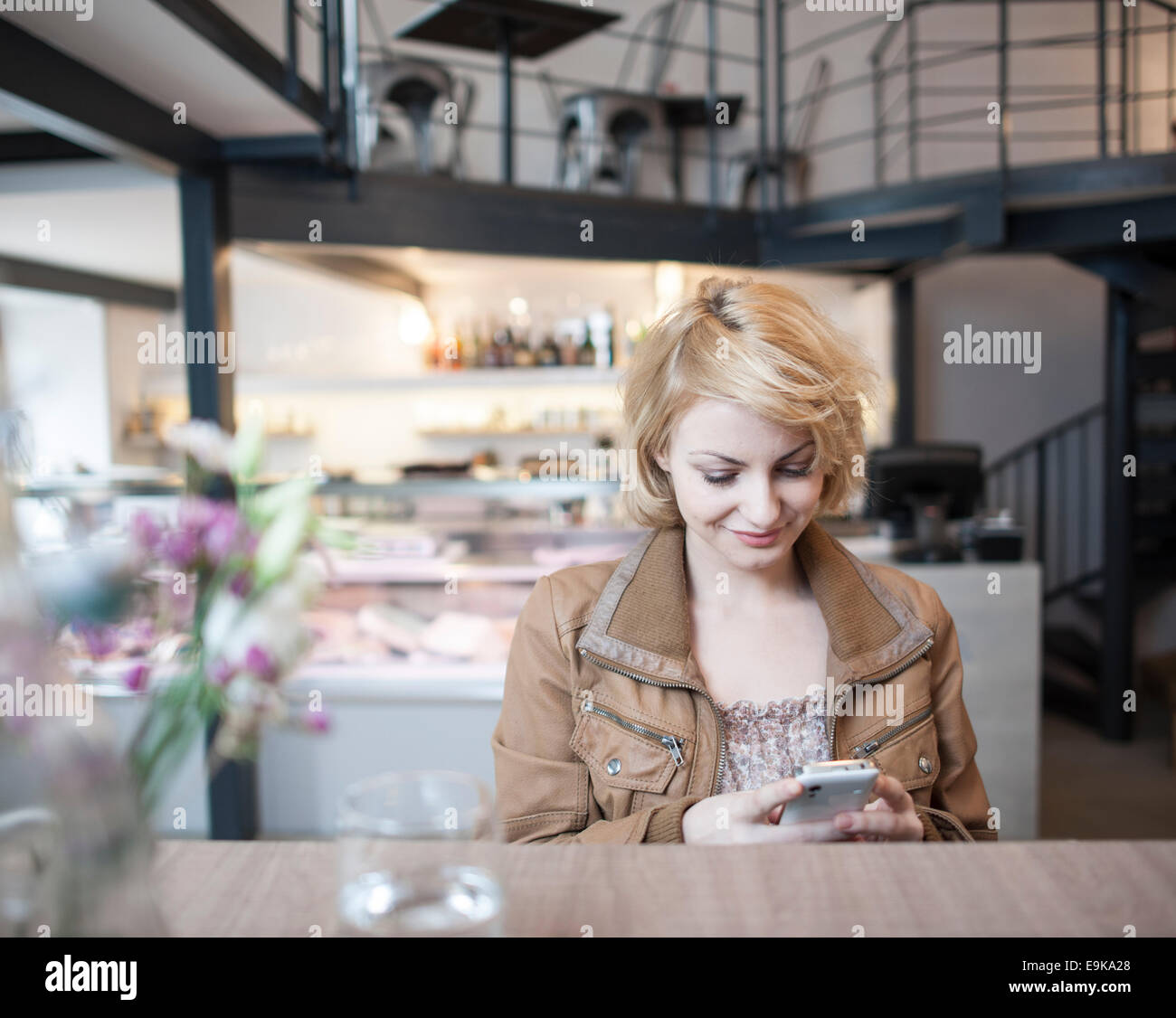 Happy young woman reading text message on cell phone in cafe - Stock Image