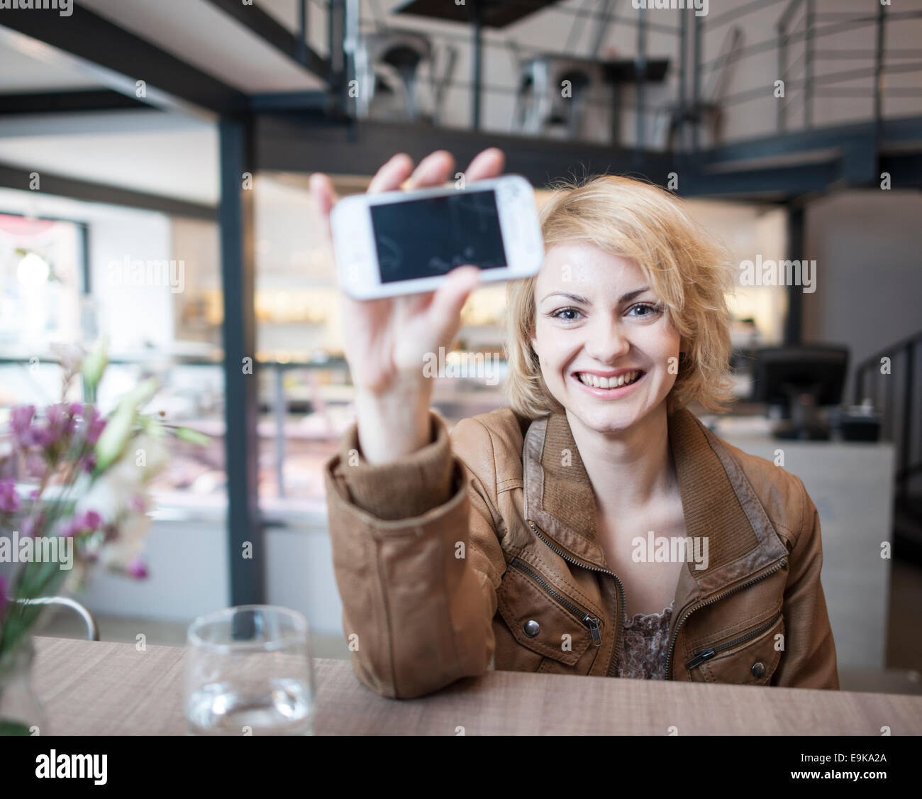 Portrait of smiling young woman displaying cell phone in cafe - Stock Image