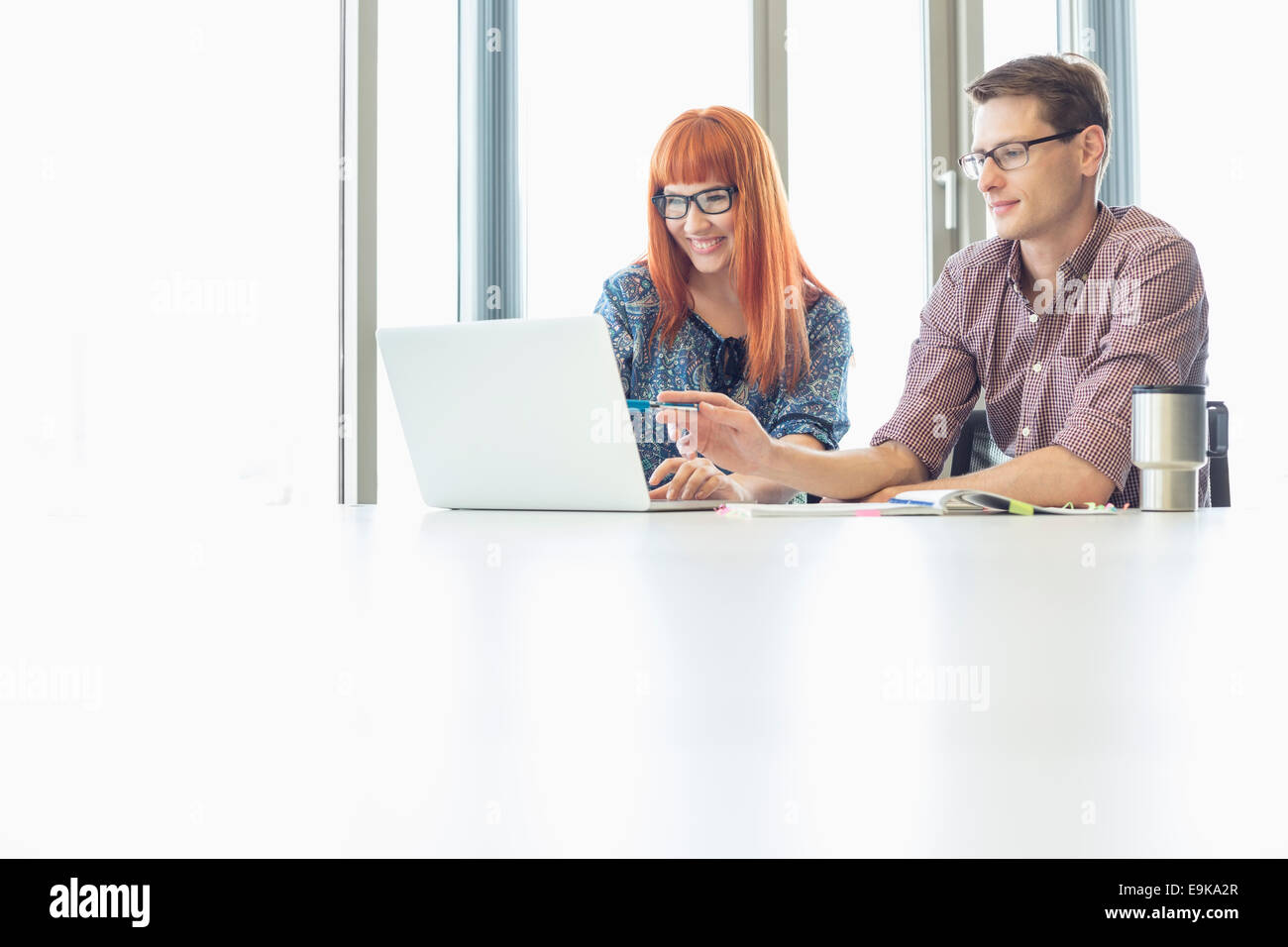 Business colleagues using laptop at desk in creative office - Stock Image