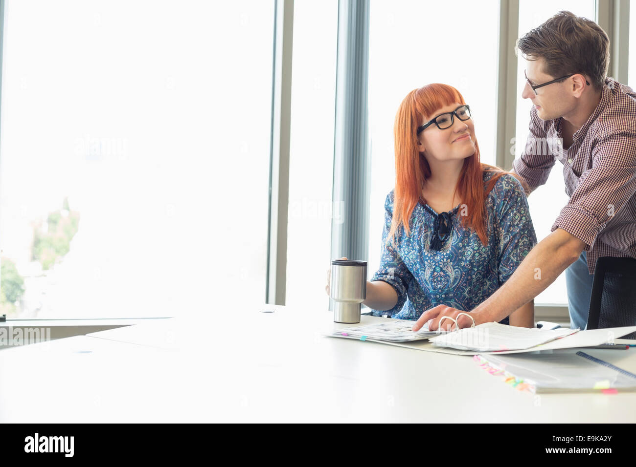 Businesspeople looking at each other while working at desk in creative office Stock Photo
