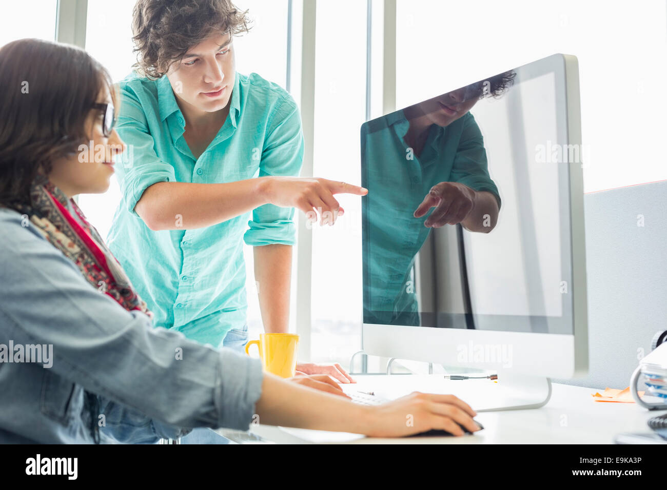 Creative businessman showing something to colleague on desktop computer in office - Stock Image