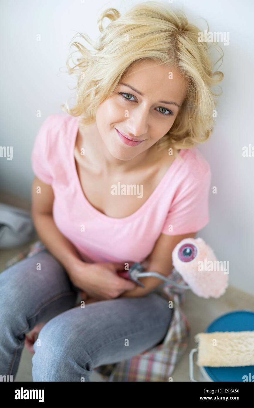Portrait of beautiful woman taking break from painting in new house - Stock Image