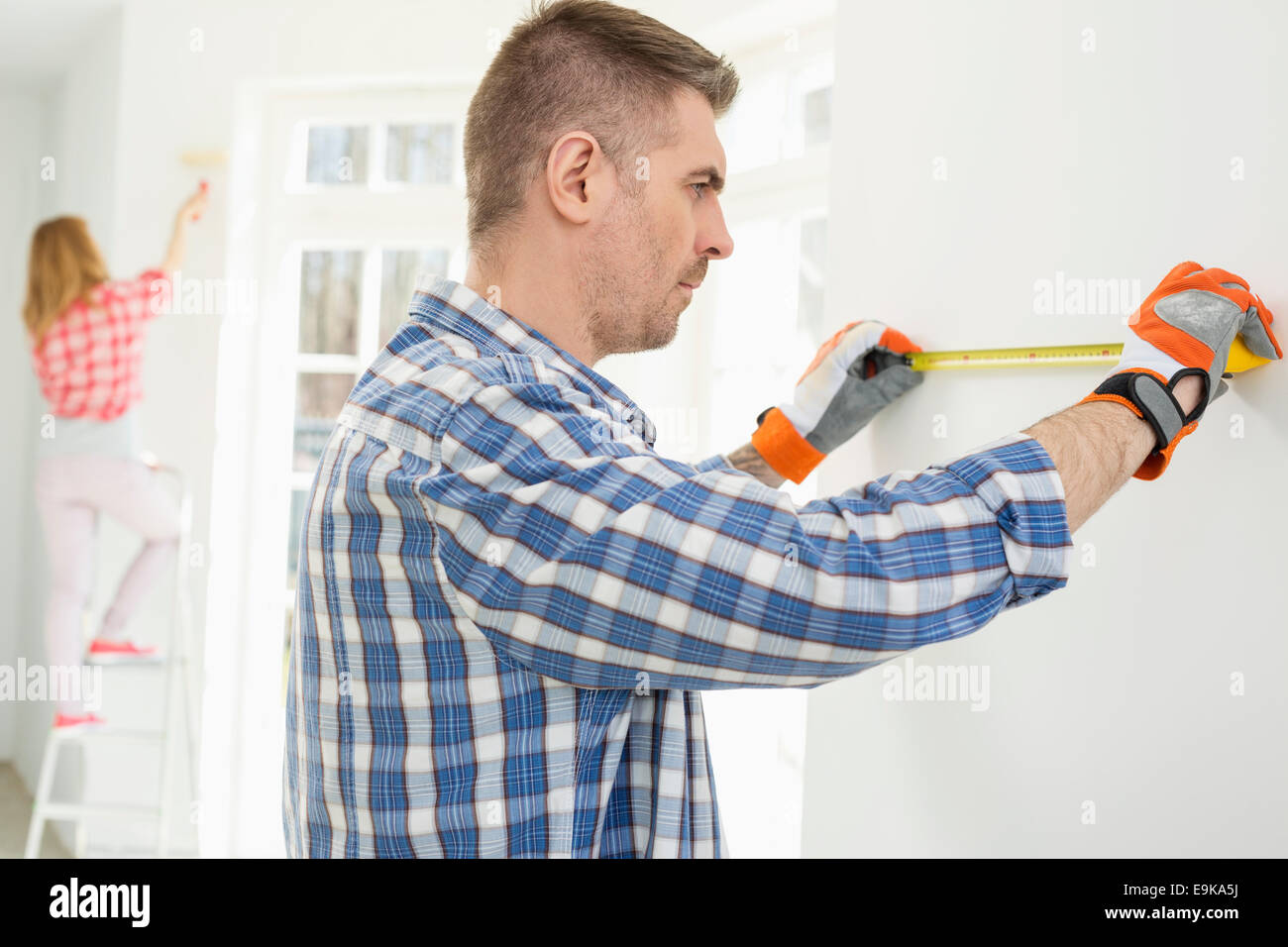 Man measuring wall with woman painting in background - Stock Image