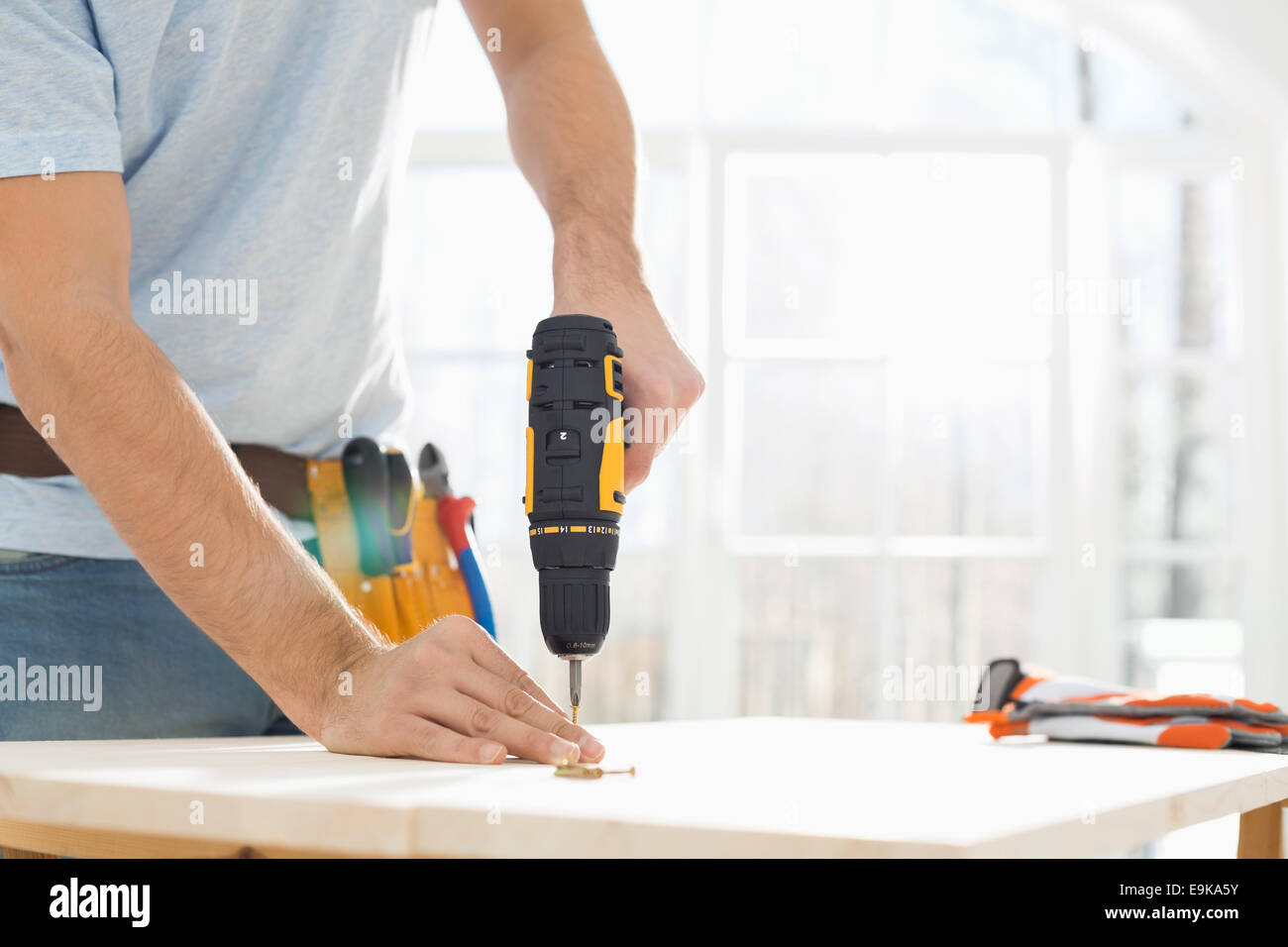 Midsection of man drilling nail on table - Stock Image