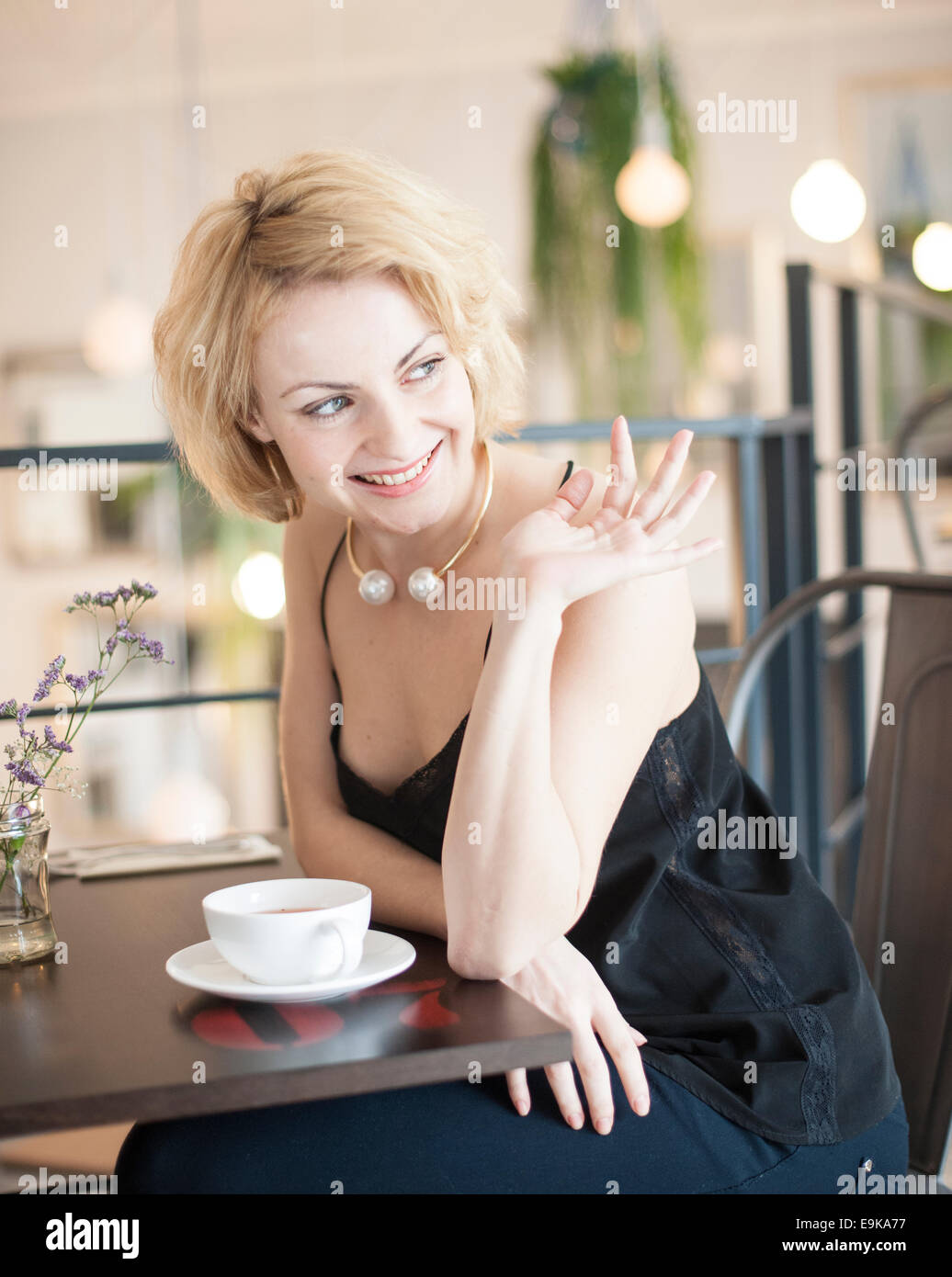 Happy young woman waving at restaurant table - Stock Image