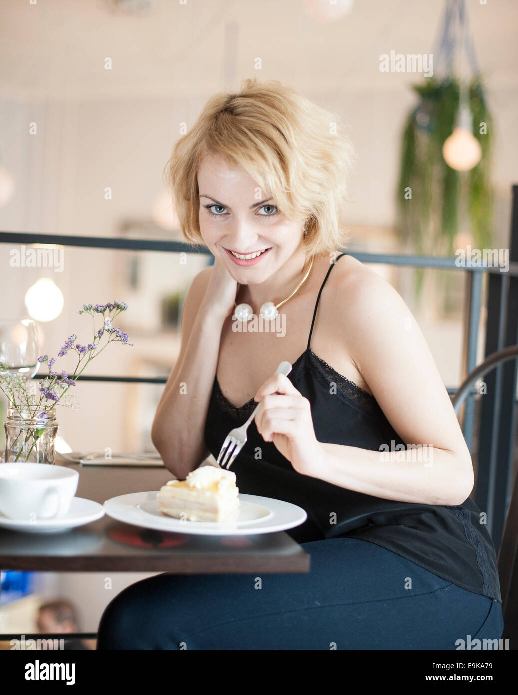 Portrait of happy young woman eating cake at cafe Stock Photo